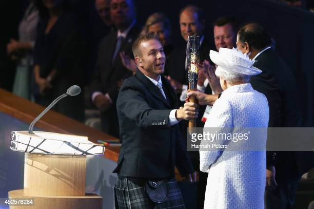 Sir Chris Hoy presents Prince Imran the CGF President the baton as Queen Elizabeth II Patron of the CGF looks on during the Opening Ceremony for the...