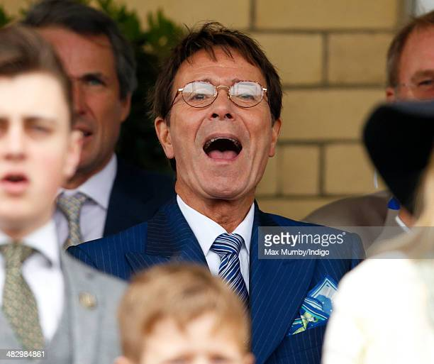 Sir Cliff Richard cheers whilst watching the racing as he attends the Crabbie's Grand National horse racing meet at Aintree Racecourse on April 5...