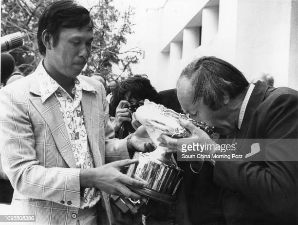 Sir Denys Roberts is first to take a sip of champagne from the Hongkong Open Golf championship trophy won at Fanling yesterday by Taiwan's Ho...