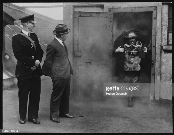 Sir Douglas Ritchie watches as a firefighter carries a 'victim' from a smokefilled room during a fire fighting and rescue exercise staged by Air Raid...