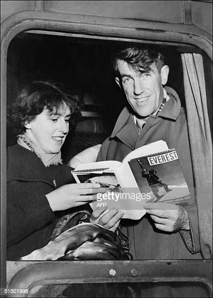 Sir Edmund Hillary and his wife display in January 1954 a bood about his victory over Mt Everest as they arrive in a train in Val D'Isere Hillary...