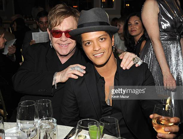 Sir Elton John and Bruno Mars during the auction following the Revlon concert for the Rainforest Fund at The Pierre Hotel on April 3 2012 in New York...