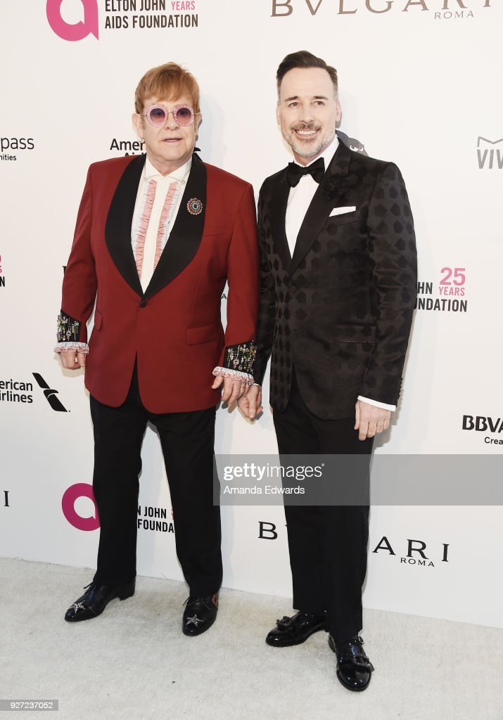 Sir Elton John (L) and David Furnish arrive at the 26th Annual Elton John AIDS Foundation's Academy Awards Viewing Party on March 4, 2018 in West Hollywood, California.