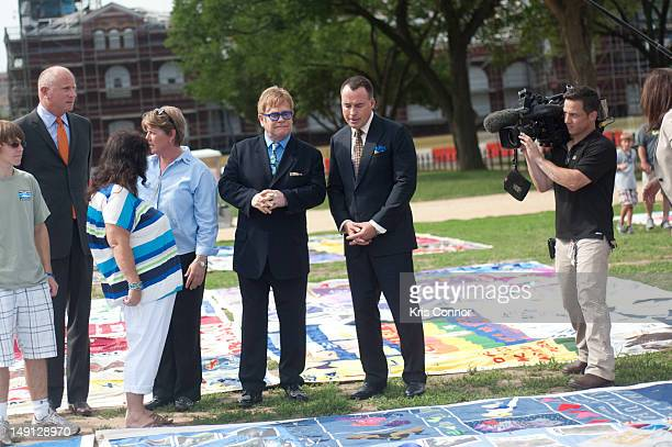 Sir Elton John and David Furnish pose for a photo during a visit to the AIDS Memorial Quilt at the National Mall on July 23 2012 in Washington DC