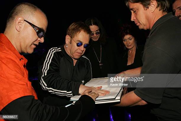 Sir Elton John makes his handprint in the official book under the watch of Ozzie and Sharon Osbourne as he records his contribution to the new...