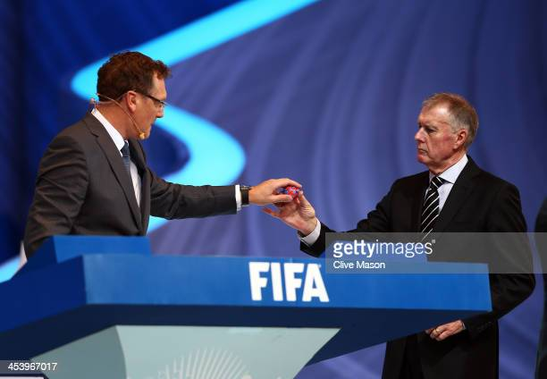 Sir Geoff Hurst passes one of the draw balls to FIFA Secretary General Jerome Valcke during the Final Draw for the 2014 FIFA World Cup Brazil at...