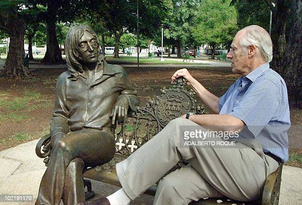 Sir George Martin known worldwide as the fifth Beatle from his collaborations with the famous musical group shares a seat with a statue of John...