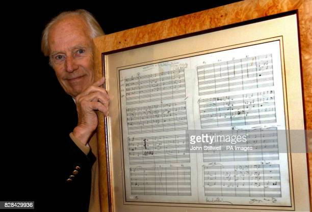 Sir George Martin the legendary record producer for The Beatles holds his limited edition lithograph of the lyrics of 'Yesterday' written by Paul...