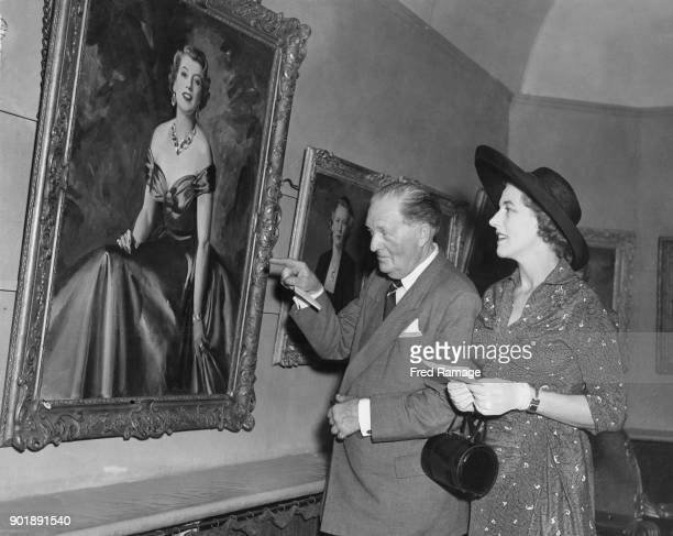 Sir Harold Bowden and June Bowden Mackay view a portrait of her during a private view of paintings by Cowan Dobson at the Cooling Galleries in London...