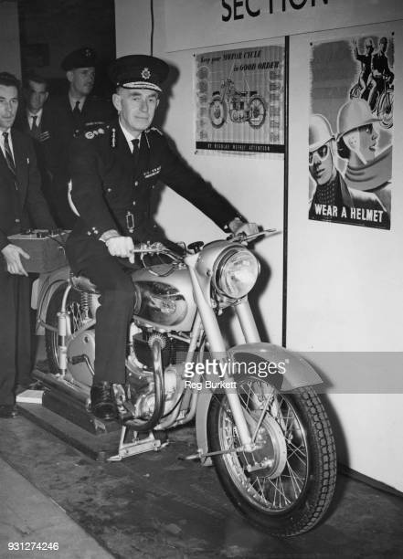 Sir John NottBower Commissioner of Police of the Metropolis tries out a motorcycle reaction tester after opening the Better Roadmanship Exhibition at...