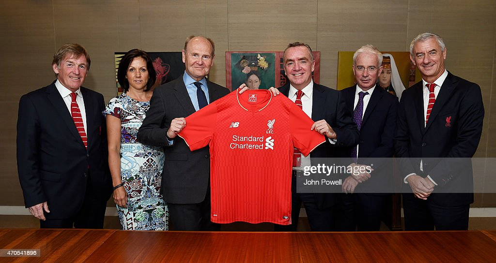 Sir John Peace Chairman of Standard Chartered (3rd L) and Ian Ayre, Chief Executive of Liverpool Football Club (4th L) pose with Kenny Dalglish (L), Non Executive Director, Ian Rush L.F.C. Ambassador (R), Tracy Clarke, Director Compliance, People and Communications (2nd L) and Peter Sands, (2nd R) Group Chief Executive from Standared Chartered Bank as Liverpool FC and Standard Chartered Bank announce a three year extension to the main sponsor agreement on April 21, 2015 in London, England.