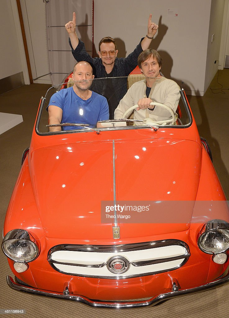 Sir Jonathan Ive, Marc Newson and Bono hop into a unique red Fiat Jolly, one of the 44 extraordinary items to be sold at the (RED) Auction this Saturday, 23rd November, at Sotheby's New York. Curated by Jony and Marc, the (RED) Auction features a collection of unique design objects – with pieces ranging from space travel and lighting design to contemporary art and rare automobiles. Proceeds from the sale will benefit The Global Fund to fight AIDS. Two entirely new pieces created by Ive and Newson feature in the Auction; A one-off 'Leica M for (RED)' digital camera, and a '(RED) Desk'. Other highlights include unique pieces by Range Rover, Hermès, Dom Pérignon, Steinway & Sons, Azzedine Alaïa and Jaeger-LeCoultre. The Fiat Jolly in which Jony, Marc and Bono are photographed has been specially liveried for the (RED) Auction, finished in red and outfitted with Jolly equipment including wicker seats and a surrey top. Photo taken at Sotheby's on November 21, 2013 in New York City. (Photo by Theo Wargo/Getty Images for (RED))