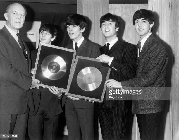 Sir Joseph Lockwood chairman of EMI presents the Beatles with two silver discs to mark the 1/4 million plus sales of their two long playing records...