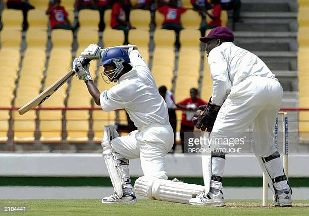 Sir Lanka's batsman Kumar Sangakkara drives West Indies bowler Mervin Dillon 20 June as West Indies Keeper Ridley Jacobs looks on during his half...