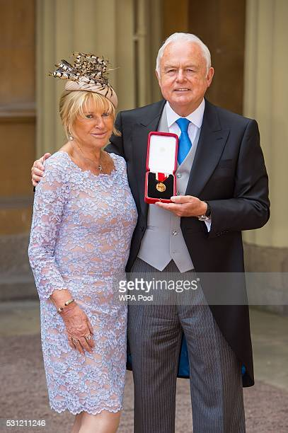 Sir Martyn Lewis and his wife Penny poses after he was awarded a knighthood from the Duke of Cambridge at an investiture ceremony at Buckingham...