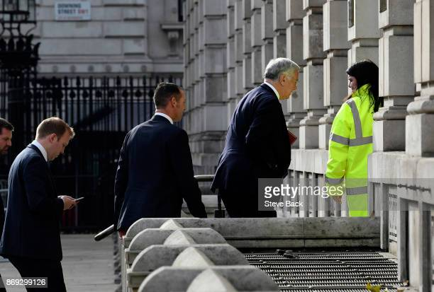 Sir Michael Fallon arrives with a close protection officer and a Conservative Party worker at the Cabinet Office on November 1 2017 in London United...
