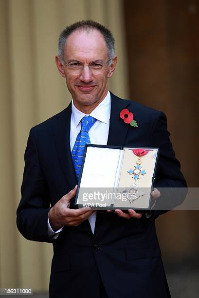 Sir Michael Moritz poses after receiving a Knighthood from Queen Elizabeth II during an Investiture ceremony at Buckingham Palace on October 30 2013...