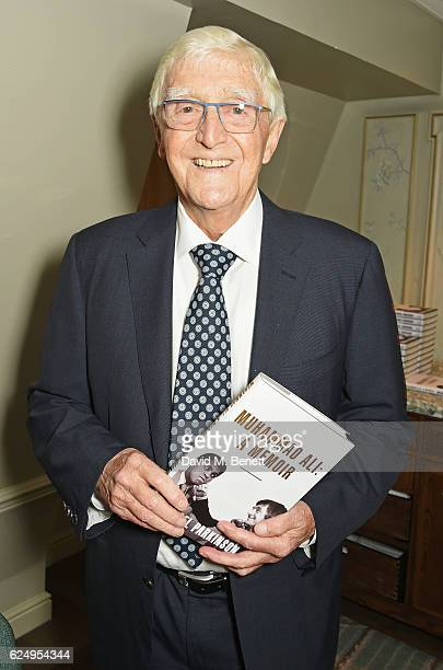 Sir Michael Parkinson poses with his new book 'Muhammad Ali A Memoir' at Fortnum Mason on November 21 2016 in London England