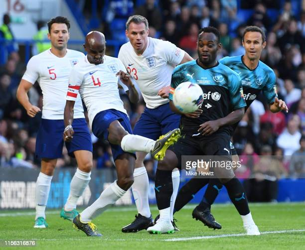 Sir Mo Farah of England clears from Michael Essien of Soccer Aid World XI during the Soccer Aid for UNICEF 2019 match between England and the Soccer...