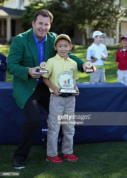 Sir Nick Faldo of England presents the winner's trophy to Jay Leng Jr at the prizegiving for the Boys 79 division during the Drive Chip and Putt...