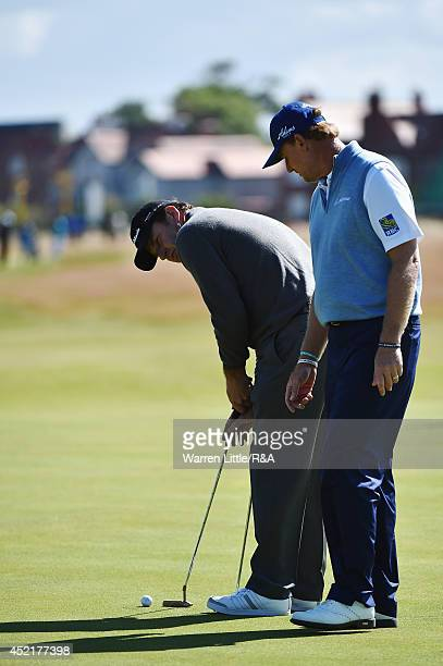 Sir Nick Faldo of England putts alongside Ernie Els of South Africa during a practice round prior to the start of The 143rd Open Championship at...