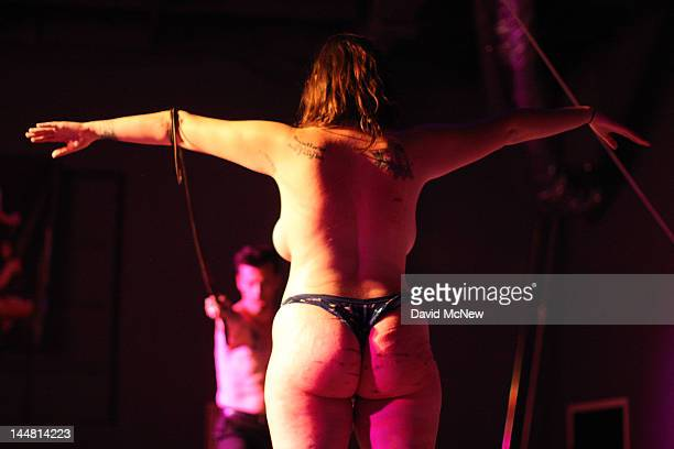 Sir Nik uses a bullwhip on a woman who is a willing submissive participant at a dungeon party during the DomConLA convention on May 18 2012 in Los...