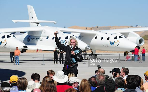Sir Richard Branson addresses a crowd of guests and media in front of WhiteKnightTwo, with the SpaceShipTwo vessel in the middle, at Spaceport...