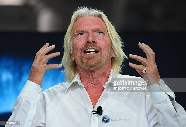Sir Richard Branson gestures while speaking on stage inside the hangar at Spaceport America northeast of Truth Or Consequences, on October 17, 2011...