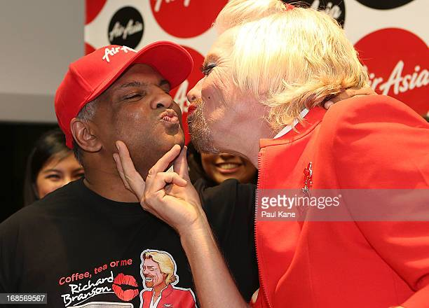 Sir Richard Branson gives Tony Fernandes a kiss before boarding his flight to Kuala Lumpur at Perth International Airport on May 12 2013 in Perth...