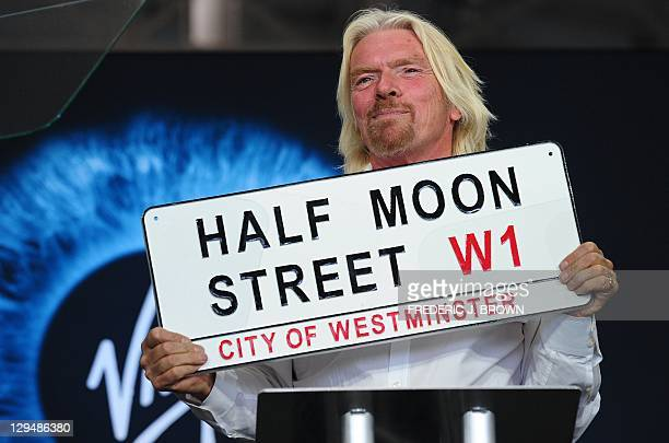 Sir Richard Branson holds a plaque from Virgin Galactic's London offices during a ceremony inside the hangar facility at Spaceport America, northeast...