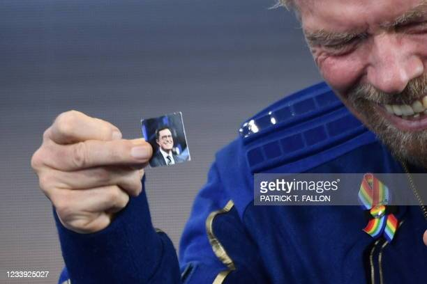 Sir Richard Branson holds up a photo of comedian Stephen Colbert that he brought with him into space, as he speaks after flying into space aboard a...