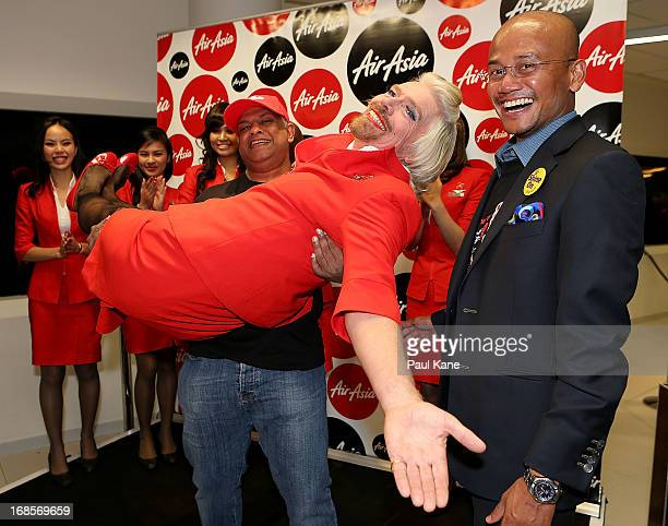 Sir Richard Branson is held in the arms of Tony Fernandes prior to their flight to Kuala Lumpur at Perth International Airport on May 12 2013 in...