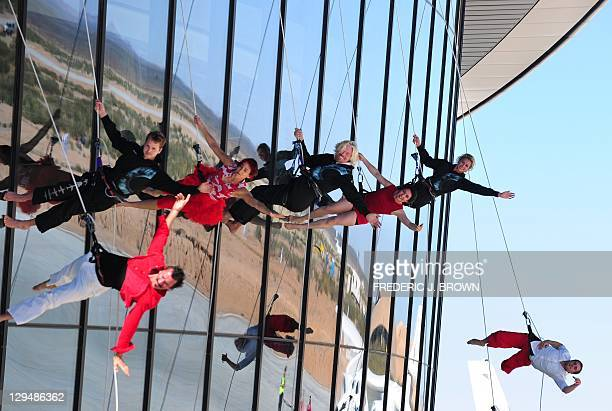 Sir Richard Branson joins performers mimicking the motion of flight while abseiling down the exterior of the hangar facilty at Spaceport America,...