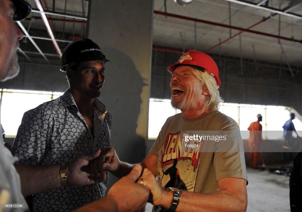 Sir Richard Branson (R) laughs, watched by Chad Le Clos, during his visit to the new Virgin Active Sandton under construction on February 27, 2013, in Johannesburg, South Africa.