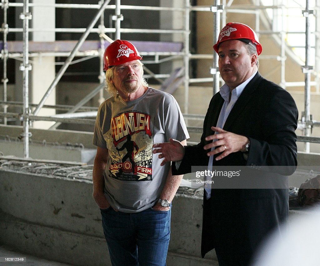 Sir Richard Branson (R) listens as Ross Faragher-Thomas speaks, during his visit to the new Virgin Active Sandton under construction on February 27, 2013, in Johannesburg, South Africa.