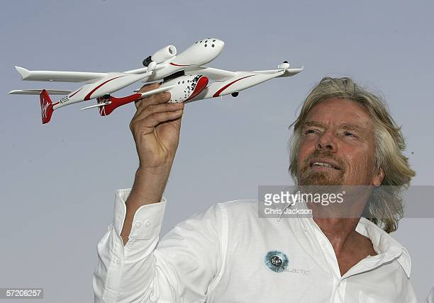 Sir Richard Branson poses a model of 'Spaceship One' after a Press conference for Virgins new service Virgin Galactic at Emirates Towers on March 29,...