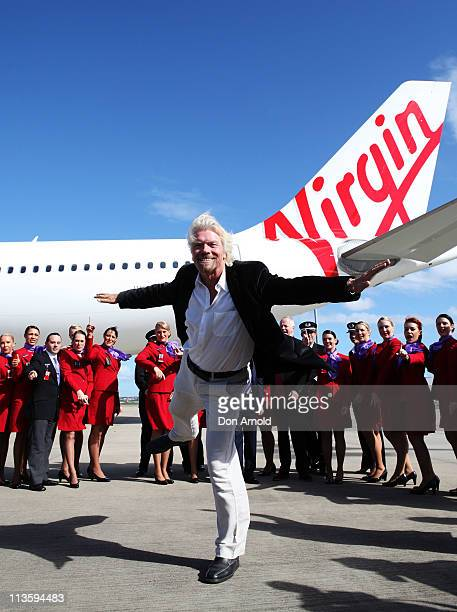 Sir Richard Branson poses alongside staff members during a rebranding launch which saw Virgin Australia replace Virgin Blue and V Australia at Sydney...
