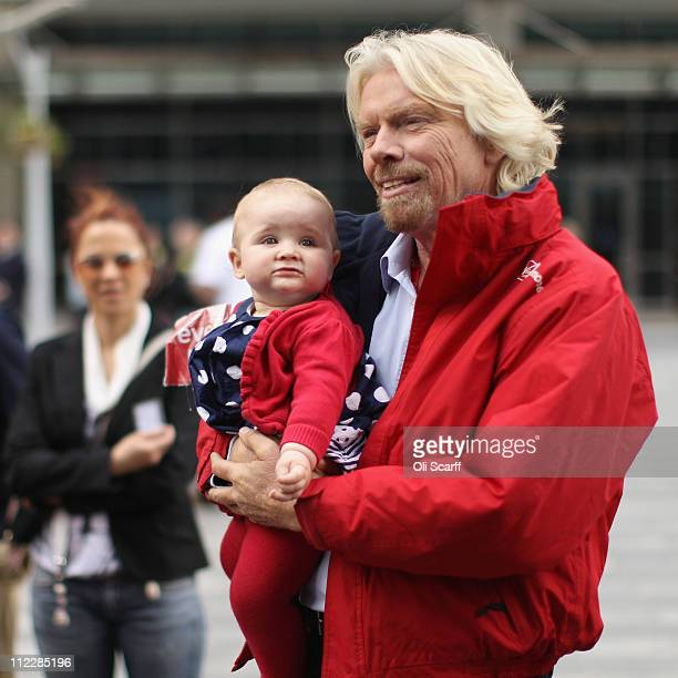 Sir Richard Branson poses for a photograph with a baby in Canary Wharf during the 2011 Virgin Money London Marathon on April 17 2011 in London...