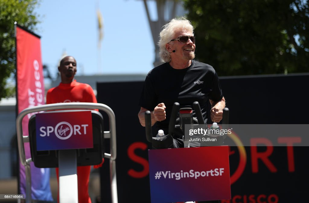 Sir Richard Branson rides an exercise bike during a news conference to announce the launch of Virgin Sport on May 18, 2017 in San Francisco, California. Virgin Group founder Sir Richard Branson announced Virgin Sport San Francisco, a half marathon run and fitness festival that is scheduled for October 14.