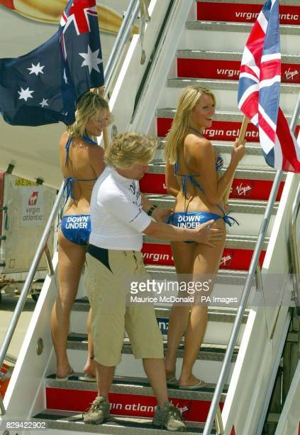 Sir Richard Branson stands on the steps of his new aircraft 'inspecting' two models holding flags from the UK and Australia after he landed at Sydney...