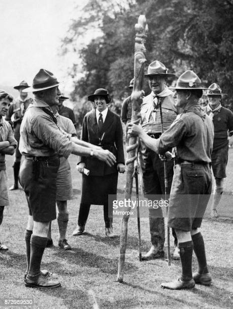 Sir Robert BadenPowell founder of the Scouts Youth movement hands a memento totem pole to a South African delegate at the 3rd World Scout Jamboree...