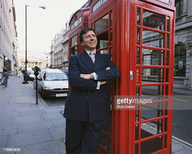 Sir Rocco Forte hotelier and son of Charles Forte poses for a photograph leaning against a red telephone phone box outside his office at Savannah...