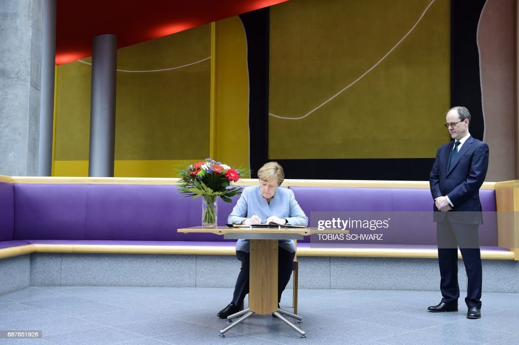 Sir Sebastian Wood, Britains Ambassador to Germany (R) looks on as German Chancellor Angela Merkel writes a message in a book of condolence at the British embassy in Berlin, on May 24, 2017, following the terror attack at the Ariana Grande concert at the Manchester Arena in Manchester on May 22. Twenty two people have been killed and dozens injured in Britain's deadliest terror attack in over a decade after a suspected suicide bomber targeted fans leaving a concert of US singer Ariana Grande in Manchester. / AFP PHOTO / POOL / Tobias SCHWARZ