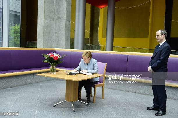 Sir Sebastian Wood Britains Ambassador to Germany looks on as German Chancellor Angela Merkel writes a message in a book of condolence at the British...