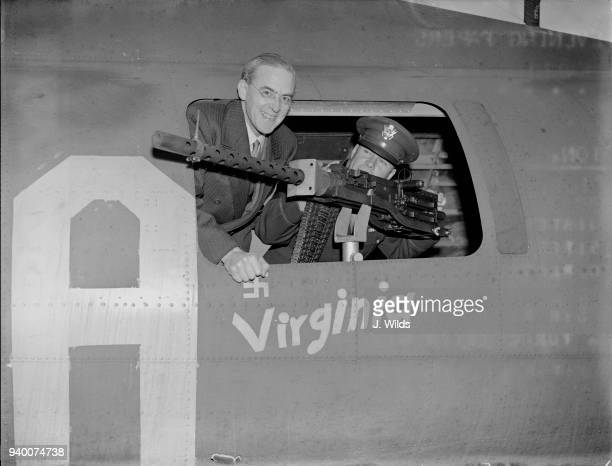 Sir Stafford Cripps Minister of Aircraft Production looks out of a waist gun turret with US Colonel Stanley T Wray during a visit to a US bomber...