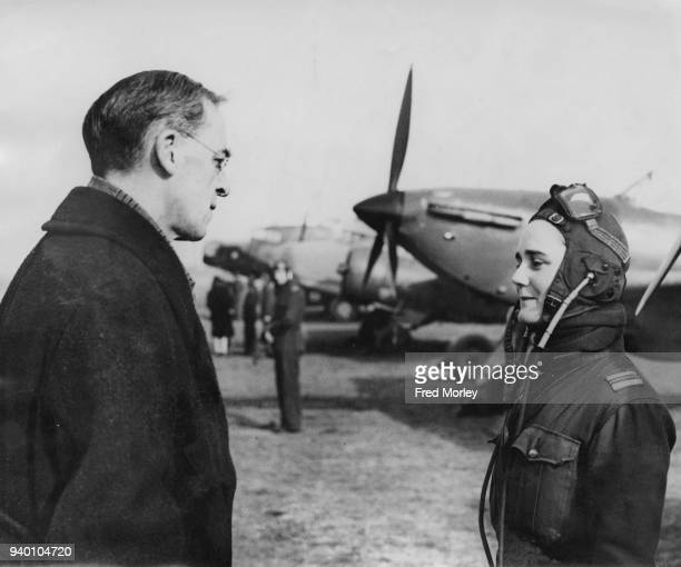 Sir Stafford Cripps the Minister of Aircraft Production talks to Flight Captain Joan Hughes a ferry pilot at an ATA Depot in England during World War...