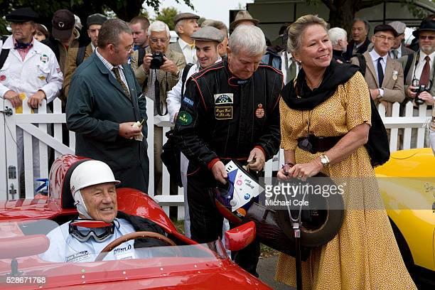 Sir Stirling Moss sitting in his 1958 OSCA FS372 with driver Roger Earl and Stirling's wife Susie on right