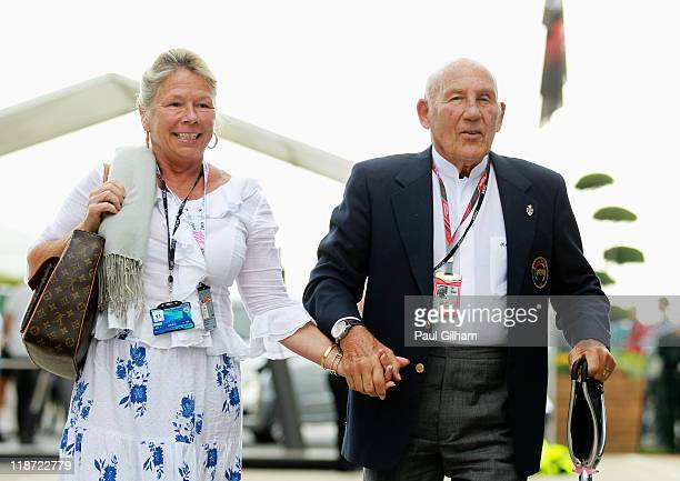 Sir Stirling Moss with his wife Lady Susie Moss arrive in the paddock before the British Formula One Grand Prix at the Silverstone Circuit on July 10...