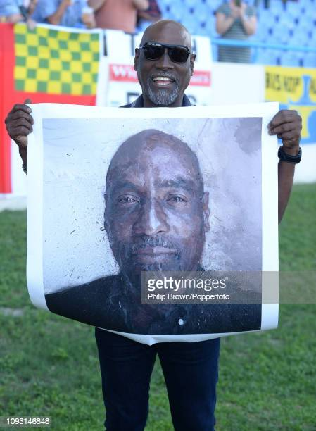 Sir Vivian Richards holds a copy of a painting presented by the MCC during the second Test match against England at the Sir Vivian Richards stadium...