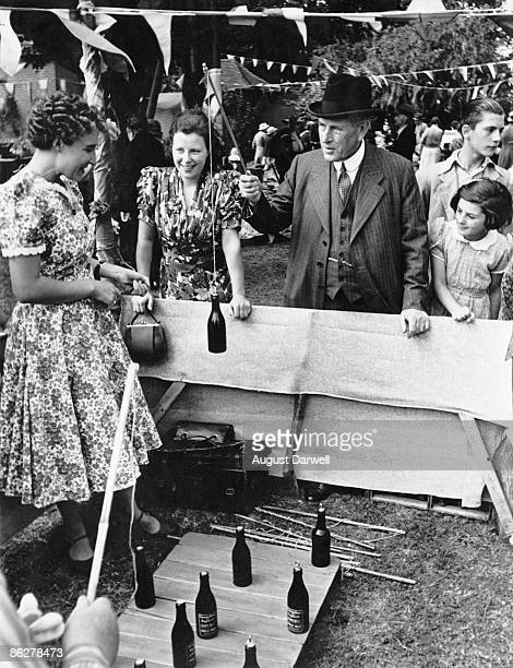 Sir William Weyland the Conservative MP for St Augustine's hooks a bottle at a fairground stall at the vicarage fete in Chislet Kent August 1939...
